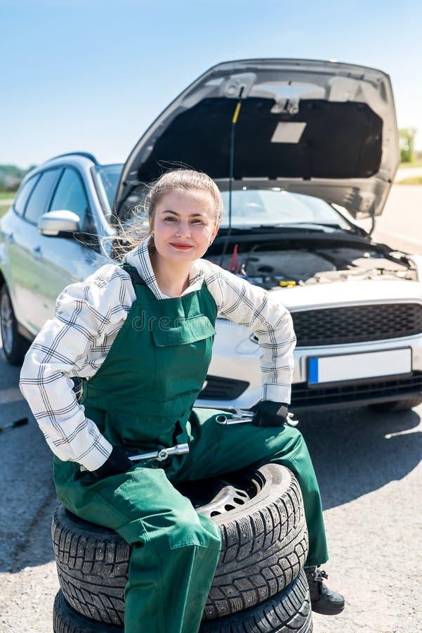 Mekaniker som poserar med däck på vägrenen med bilen arkivfoto