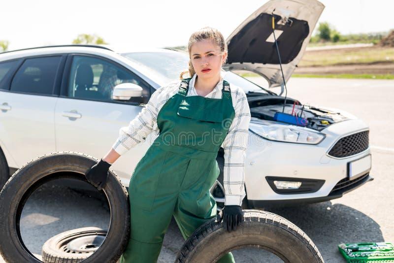 Mekaniker som poserar med d?ck p? v?grenen med bilen royaltyfri foto