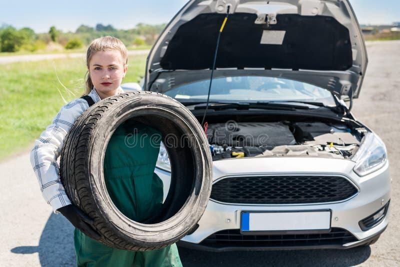 Mekaniker som poserar med d?ck p? v?grenen med bilen fotografering för bildbyråer