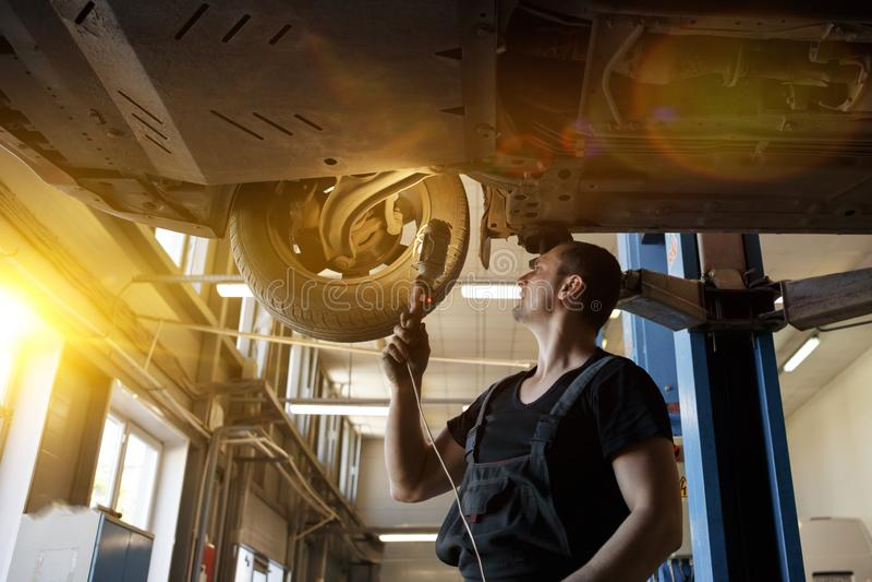 Mekaniker som in reparerar bilen utan seminariet för hjul arkivbild