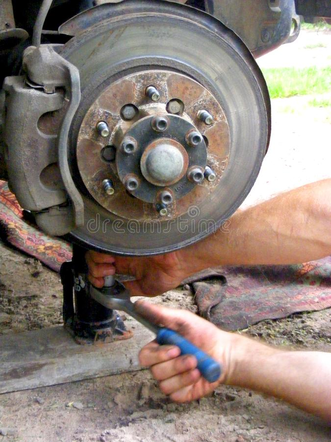 Mekaniker som reparerar en bil som bromsar, hjul royaltyfri bild