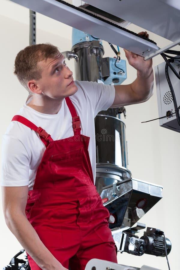 Mekaniker som reparerar fabriksmaskinen arkivbilder