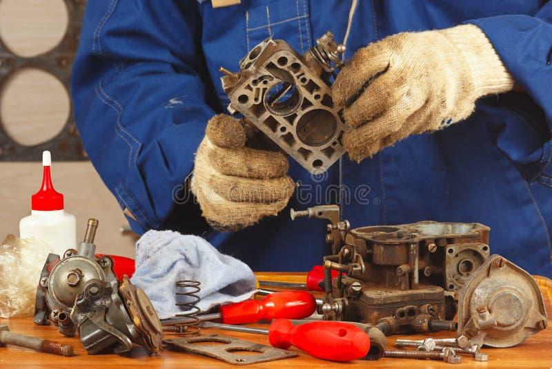 Mekaniker som reparerar gammal förgasare för bilmotor royaltyfria foton
