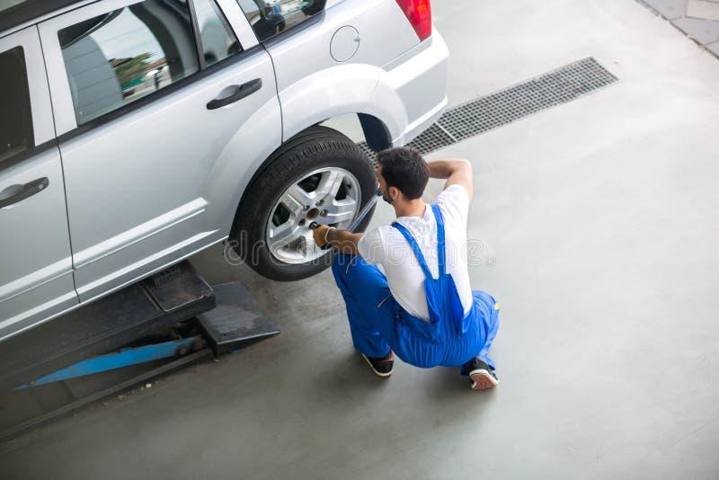 Mekaniker som tar bort ett gummihjul från en bil royaltyfri bild