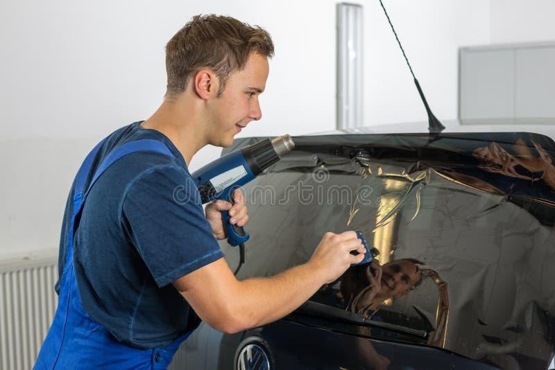 Mekaniker som tonar bilfönstret med den tonade folie eller filmen arkivfoto