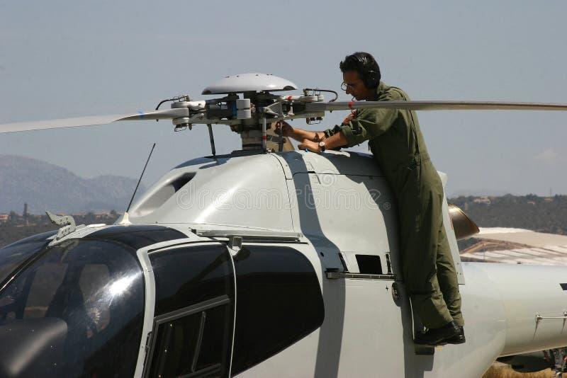 Mekaniker som vitt arbetar på akrobatiska helikoptrar för ASPA eurocopter för airshow fotografering för bildbyråer