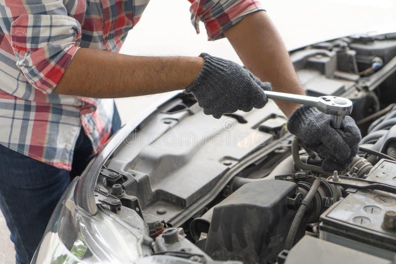 Mekaniker teknikermankontroll bilmotorn i garage Bilservice, reparation, fixande som kontrollerar underhåll som arbetar med hålig royaltyfria foton