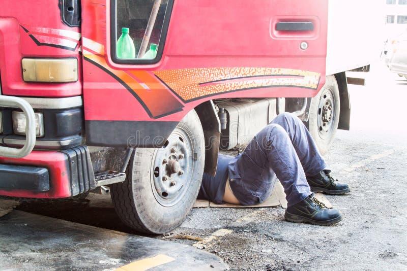 Mekaniker under lastbilen som reparerar den smutsiga fetthaltiga oljiga motorn med prob royaltyfri foto