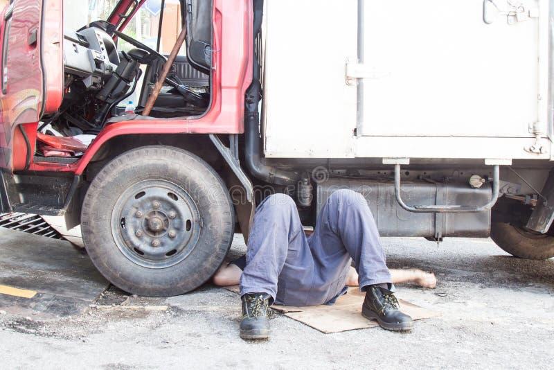 Mekaniker under lastbilen som reparing den smutsiga fetthaltiga oljiga motorn med prob royaltyfria foton