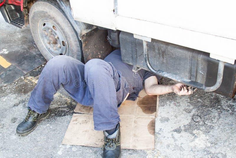 Mekaniker under lastbilen som reparing den smutsiga fetthaltiga oljiga motorn med prob arkivfoton
