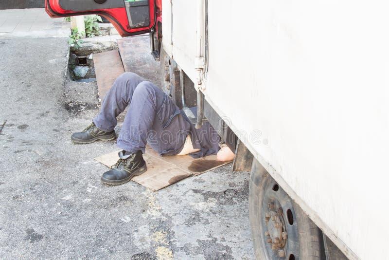 Mekaniker under lastbilen som reparing den smutsiga fetthaltiga oljiga motorn med prob fotografering för bildbyråer