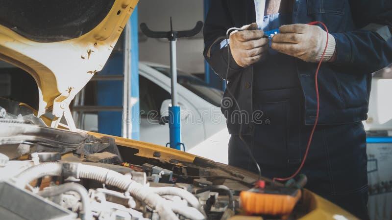 Mekanikerelkraften i bilgarageseminarium arbetar med voltmetern - elektriskt ledningsnät arkivfoto