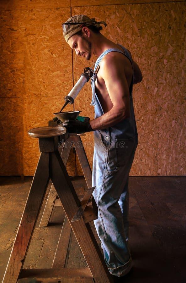 Mekanikern arbetar för att förbereda delarna för maskinen royaltyfri bild