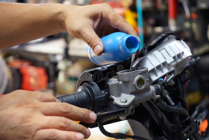 Mekanikern Check och tillfogar bromsvätska på motorcykelbromsbehållare i garage, motorcykelunderhåll och service och reparationsb royaltyfria bilder