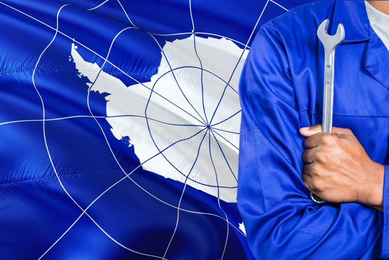 Mekanikern i blå likformig rymmer skiftnyckeln mot att vinka Antarktis flaggabakgrund Korsad armtekniker royaltyfri bild