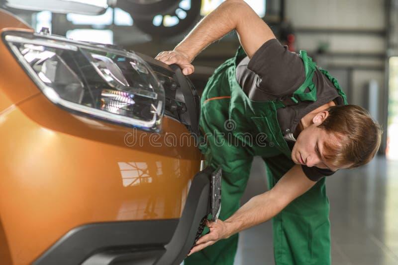 Mekanikern i de gröna overallförsöken att ta bort beklär lodis royaltyfri fotografi