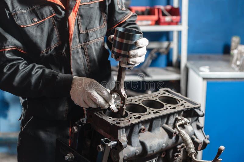 Mekanikern installerar en ny pistong Demonter medlet för motorkvarteret Motorisk huvudreparation Sexton ventiler och fyra royaltyfri fotografi