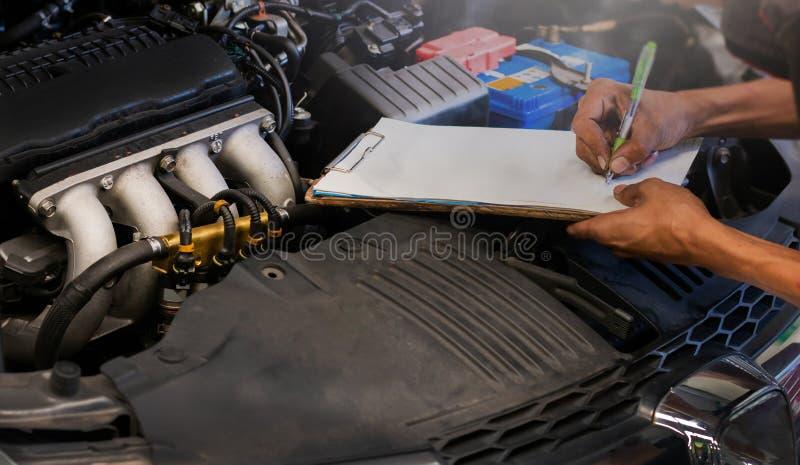 Mekanikern kontrollerar den automatiska reparationen för bilmotorn arkivbilder