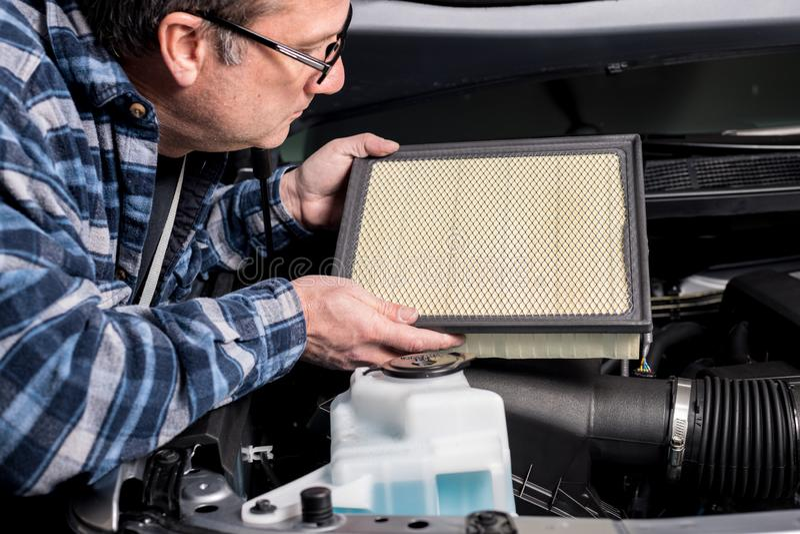 Mekanikern kontrollerar nära ett luftfilter från en uppsamling royaltyfri foto