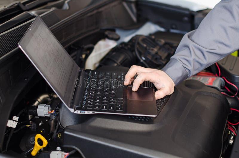 Mekanikern med bärbara datorn diagnostiserar bilen royaltyfri foto