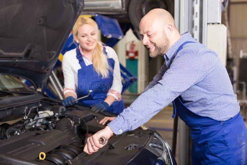 Mekanikern och assistenten som arbetar på den auto reparationen, shoppar royaltyfria bilder