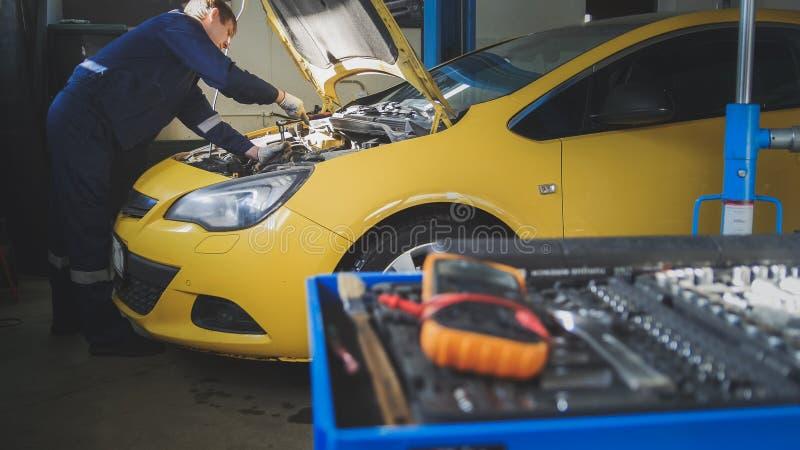 Mekanikern reparerar ett bil- skruva av detaljen av bilen - parkera bilen i garage service fotografering för bildbyråer