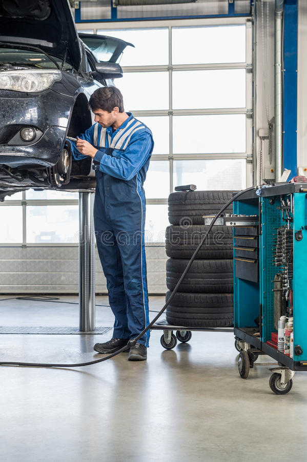 MekanikerRepairing Brake Of lyftbil på garaget royaltyfria bilder