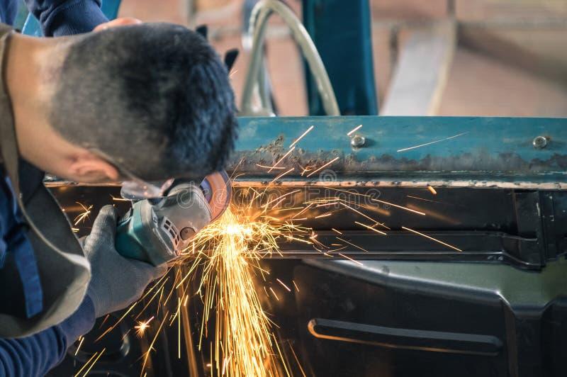 Mekanisk arbetare för ung man som reparerar en gammal tappningbilkropp royaltyfria foton