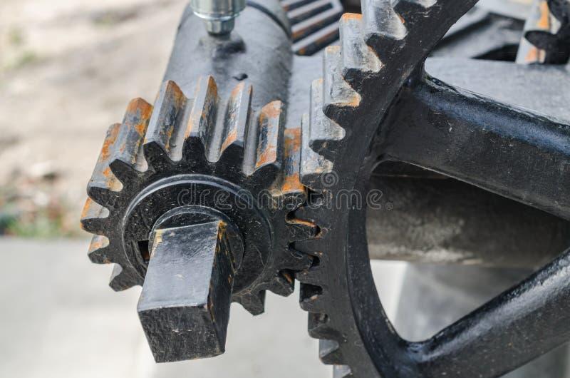Mekaniskt kugghjul för närbild med ett stort tandat hjul av dammluckan royaltyfri foto