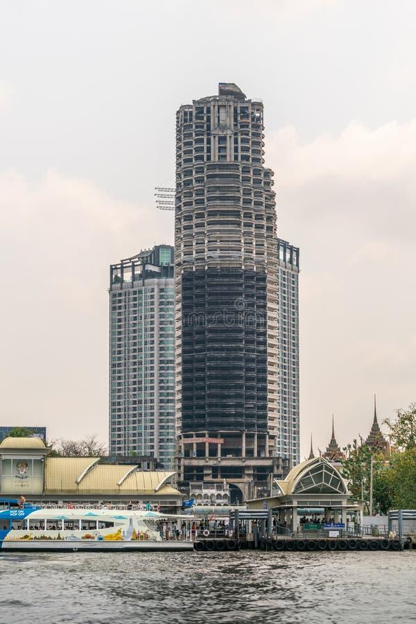 Mekhala landing at Wat Yannawa along Chao Phraya River, Bangkok Thailand. Bangkok city, Thailand - March 17, 2019: Chao Phraya River. Tall skyscraper under stock image