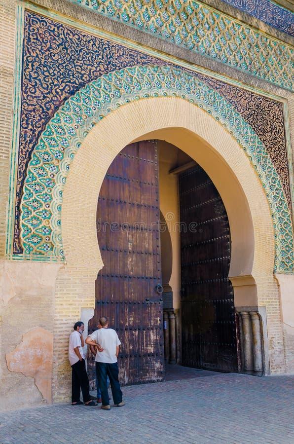 Meknes, Marrocos - 21 de agosto de 2013: Três homens marroquinos não identificados que falam na frente de Bab Mansour Gate histór fotografia de stock