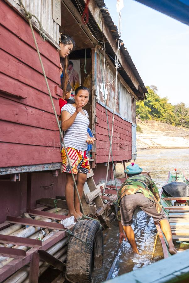 Laotian family living in a ship house. Mekong river, Laos, Feb 2016: Laotian family looking over the fence and unloading things from their floating ship house royalty free stock images