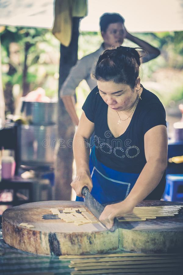 Woman who is working with a big knife a few coconut candies stock image