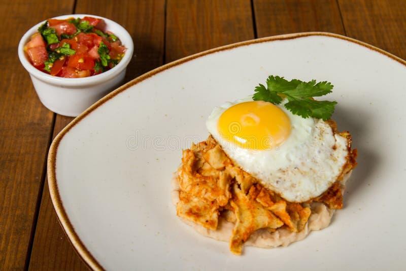 Meksykańscy śniadaniowi chilaquiles z fasolami i smażącym jajkiem na wierzchołku, z świeżym Pico De Gallo fotografia stock