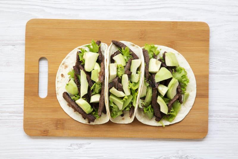 Meksykańscy tacos na bambusie wsiadają na białym drewnianym tle, odgórny widok zbliżenie Mieszkanie nieatutowy, obrazy royalty free