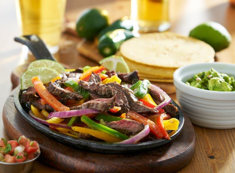 Meksykańscy wołowiien fajitas w żelaznej rynience z guacamole i piwem obrazy stock