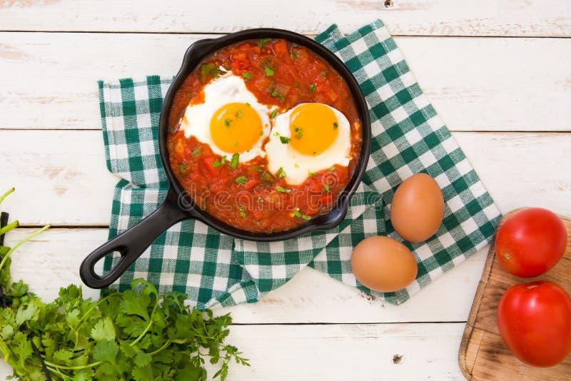 Meksykański śniadanie: Huevos rancheros w żelaznej smaży niecce na białym drewnianym stołowym odgórnym widoku fotografia stock