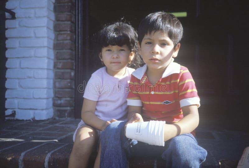 Meksykański brata i siostry obsiadanie na ich frontowych krokach, CA fotografia royalty free