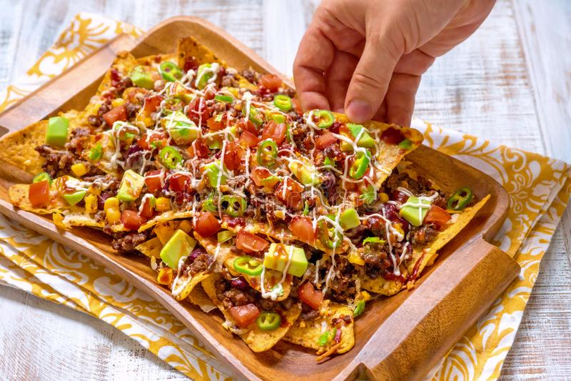 Meksykańskiego nacho kukurydzanego tortilla żółci układy scaleni z serem, mięsem, avocado guacamole i czerwień salsa, obraz royalty free