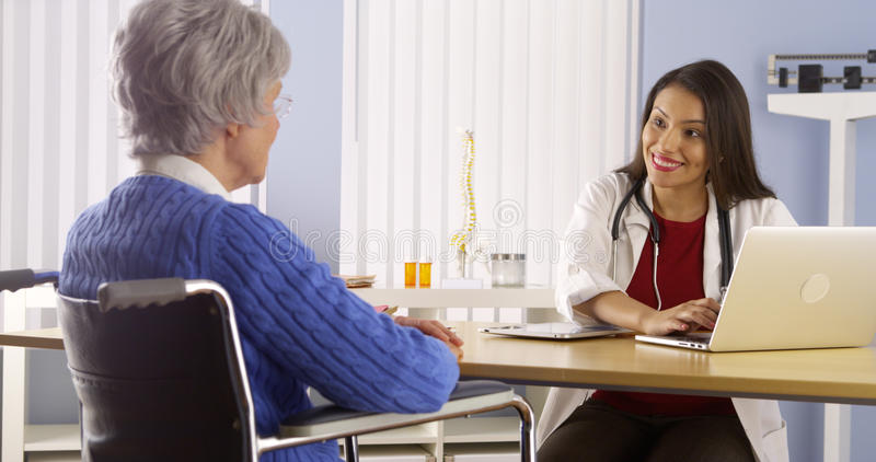 Meksykańskiej kobiety doktorski opowiadać z starszym pacjentem obrazy stock