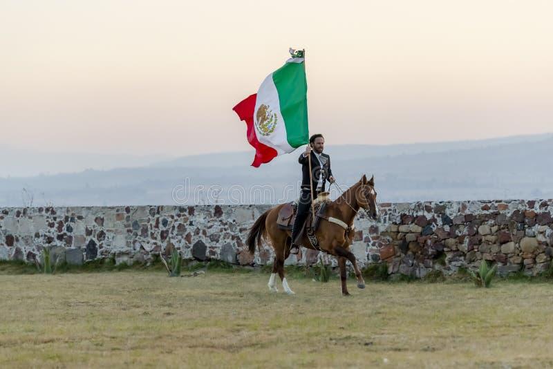 Meksykanina Charro Bardzo Przystojne pozy Przed hacjendy W Meksykańskiej wsi Podczas gdy Trzymający Meksykańską flagę obraz stock