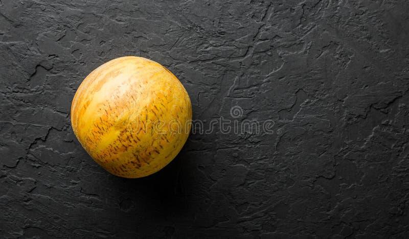 Melão amarelo inteiro no fundo de pedra preto Fruta fresca colorida Vista superior, configuração lisa, espaço da cópia fotos de stock