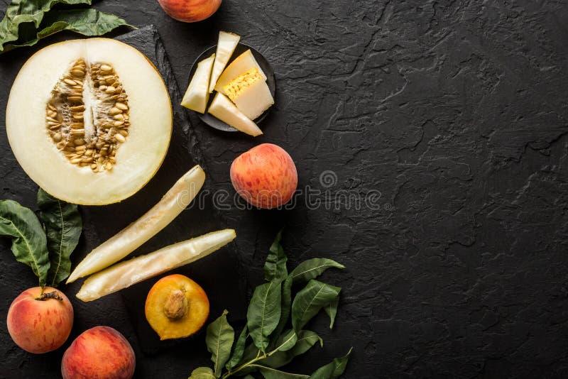 Melão e pêssegos Disposição criativa feita dos frutos Fruto fresco colorido no fundo de pedra preto imagem de stock