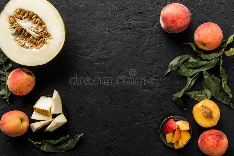 Melão e pêssegos Disposição criativa feita dos frutos Fruto fresco colorido no fundo de pedra preto imagens de stock