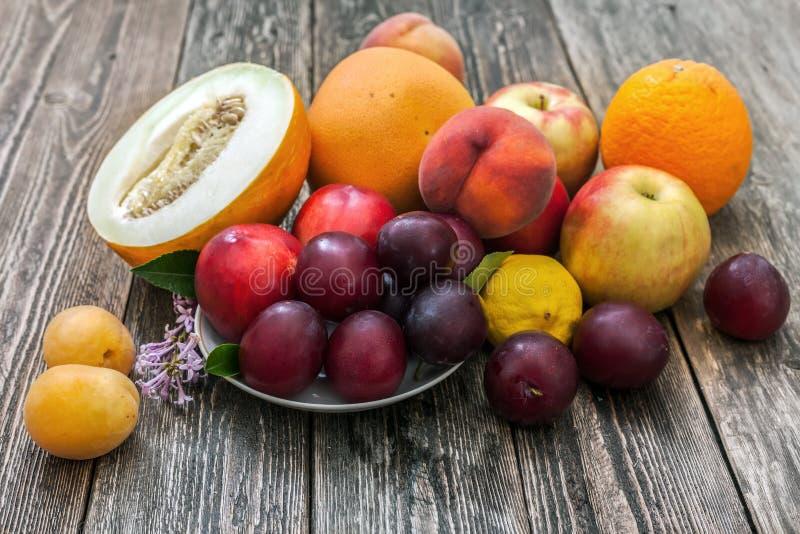 Melão, maçãs, ameixas, limão, pêssegos, abricós e toranja sobre foto de stock royalty free