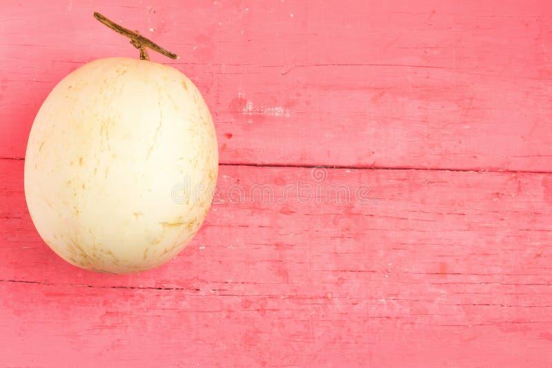 melão ( sunlady) no rosa de madeira imagem de stock