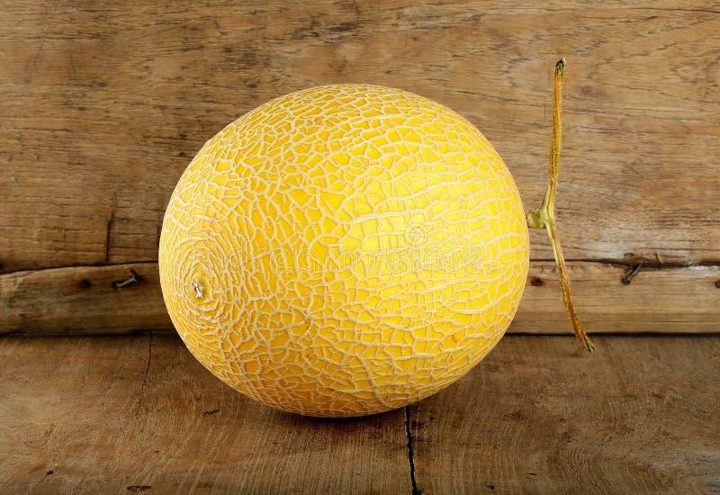 Melón amarillo del cantalupo en el fondo de madera foto de archivo