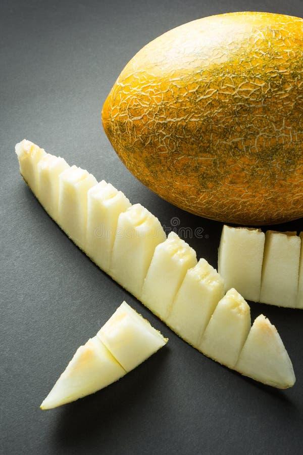 Melón amarillo y rebanadas orgánicos del cantalupo aislados en el fondo negro, vertical fotos de archivo