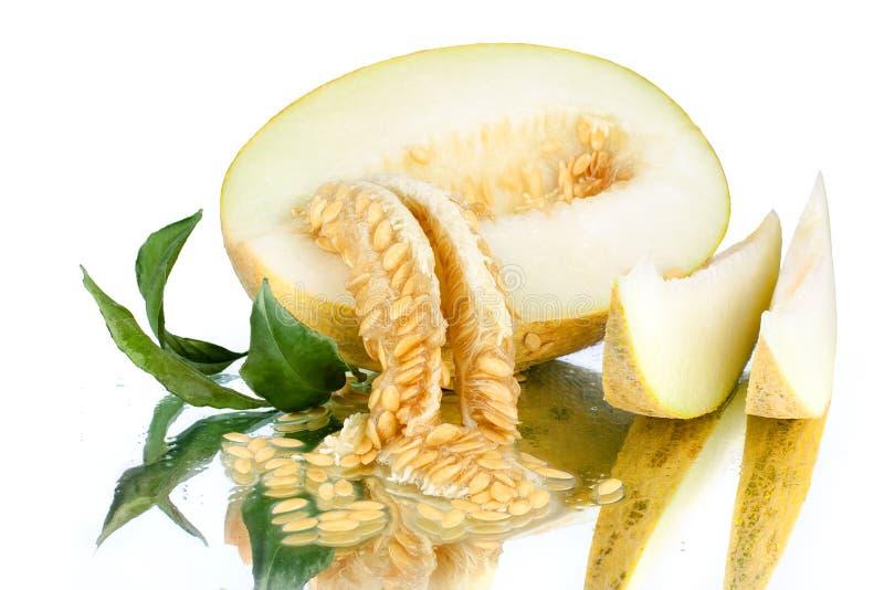 Melón cortado amarillo con las semillas en el fondo blanco del espejo aislado cerca para arriba imagen de archivo