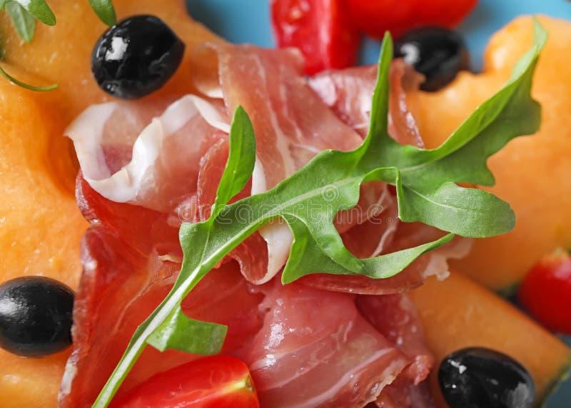 Melón delicioso con el prosciutto, las aceitunas y el arugula en la placa, primer imagen de archivo libre de regalías